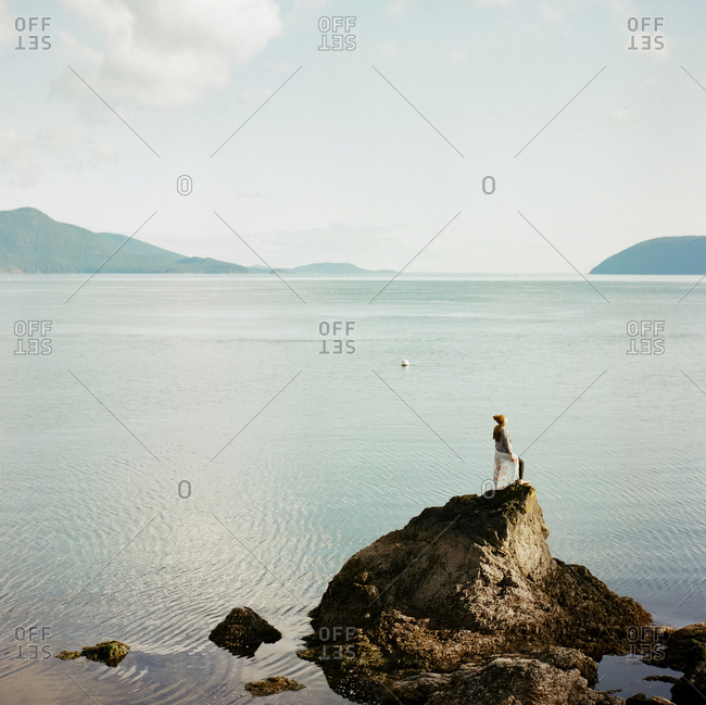 Person standing on rock along the coast of the San Juan Islands