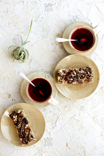 Blueberry caramelized pecan breakfast bars drizzled with dark chocolate served with hot tea