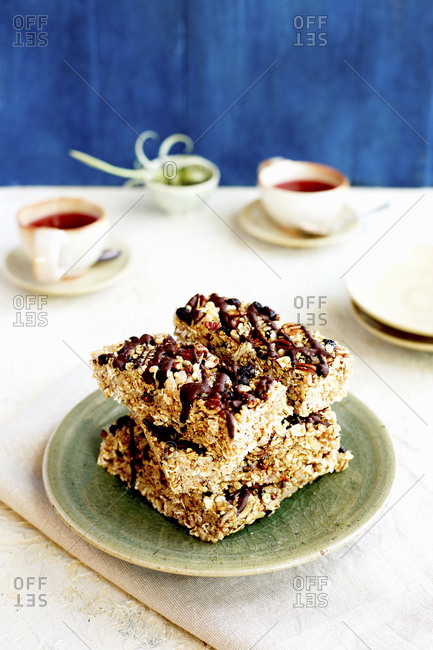 A stack of homemade blueberry caramelized pecan breakfast bars drizzled with dark chocolate