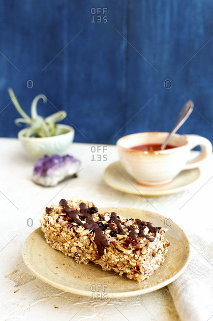 Blueberry caramelized pecan breakfast bar drizzled with dark chocolate served with a cup of tea