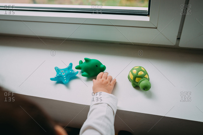 Baby playing next to the window with rubber animals