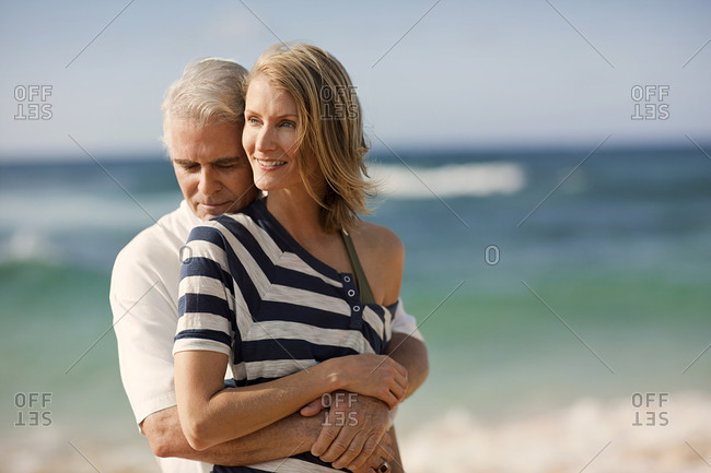 Mature man hugging his wife on the beach