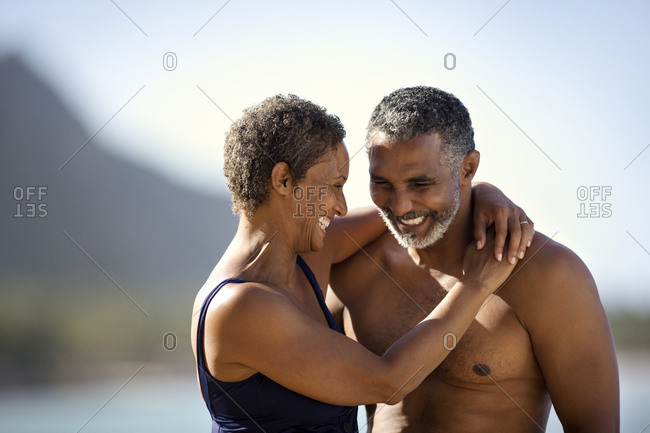 Mid adult couple standing with their arms around each other on a beach