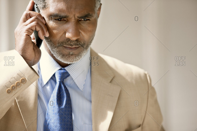 Serious mid-adult businessman talking on his cell phone