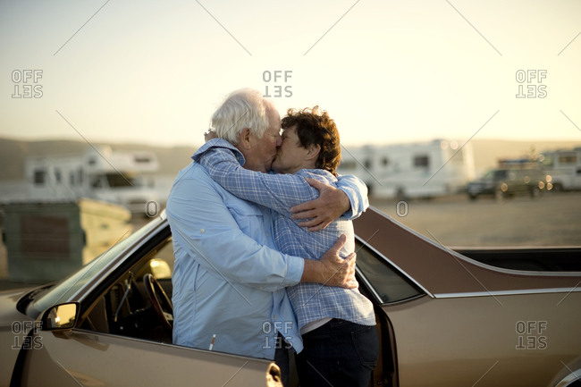 Mature couple embracing by a car