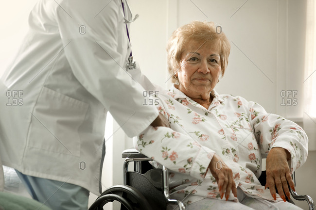 Portrait of a happy elderly woman being assisted by a female doctor while sitting in a wheelchair