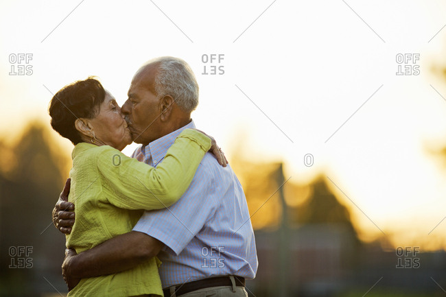 Happy senior couple kissing while standing together in the back yard