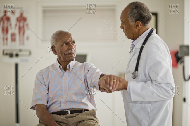 Senior man having his arm examined by a male doctor inside a doctor's office
