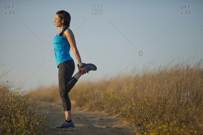 Mid adult woman doing warm up stretches before exercising