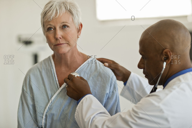 Mature woman gets her heartbeat checked by the doctor
