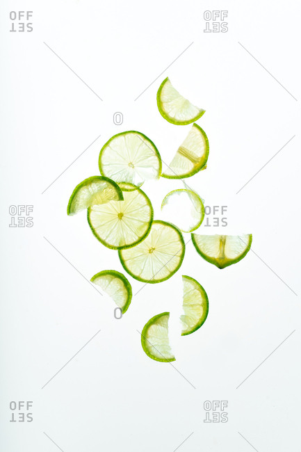 Composition with lime slices backlit on white background