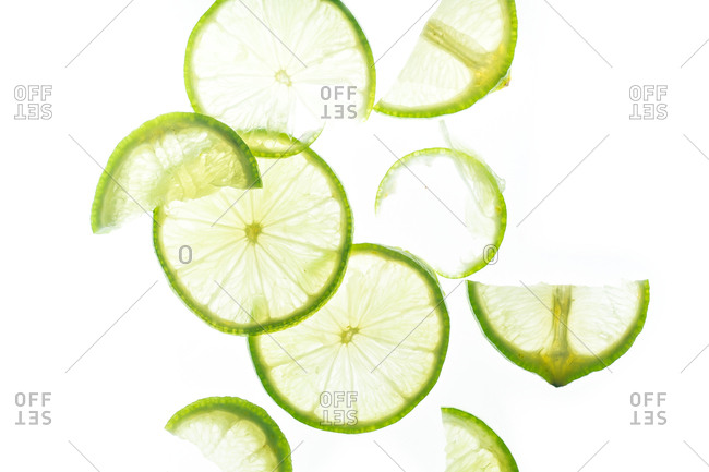 Cucumber and lime slices backlit on white background