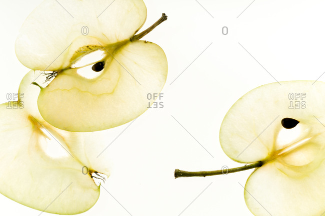 Minimalistic composition with fresh apples sliced and backlit on white background