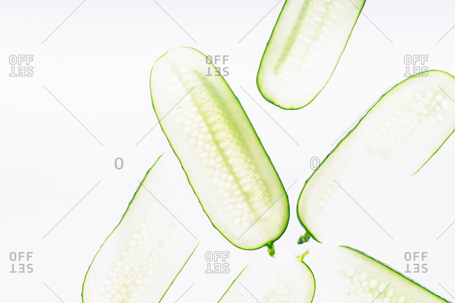 Transparent cucumber slices on white background with copy space