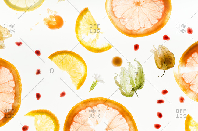Food pattern with transparent slices of citrus fruits and pomegranate seeds