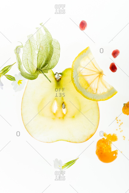 Abstract composition with transparent fruit slices and pomegranate seeds