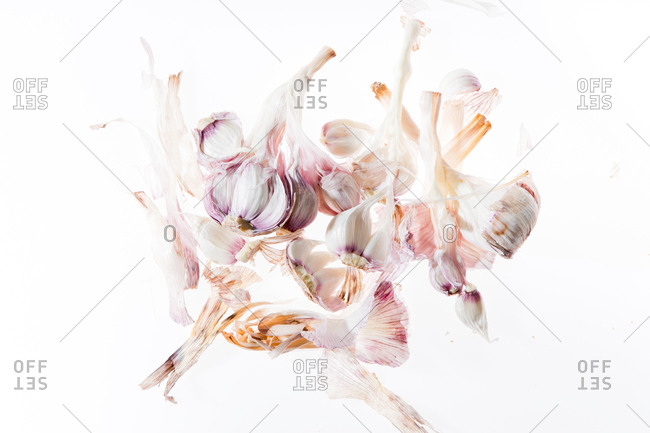 Minimalistic composition with fresh garlic on white background
