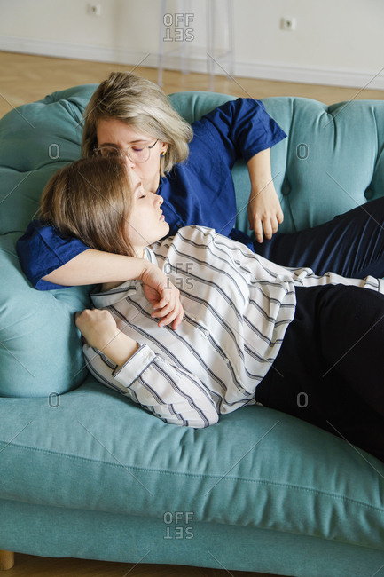Lesbian couple kissing on blue sofa at home