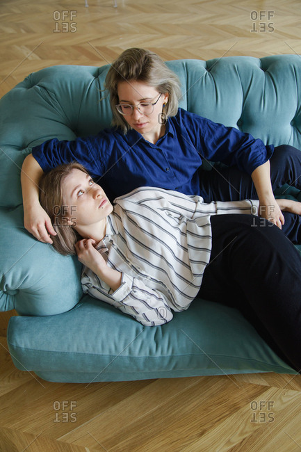 Lesbian couple spend their time together on blue sofa at home