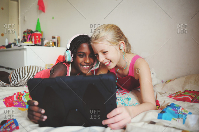 Young south Asian girl and best friend hanging out on bed watching screen of tablet computer
