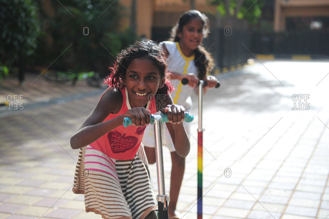 Two young South Asian girls riding their scooters outdoors