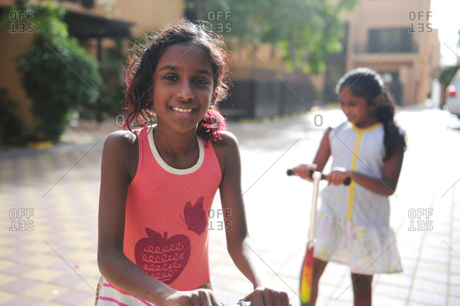 Portrait of young South Asian girl riding her scooter with twin sister in background