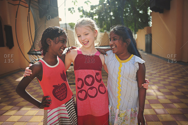 Portrait of three young girls of different ethnicities smiling and hugging each other