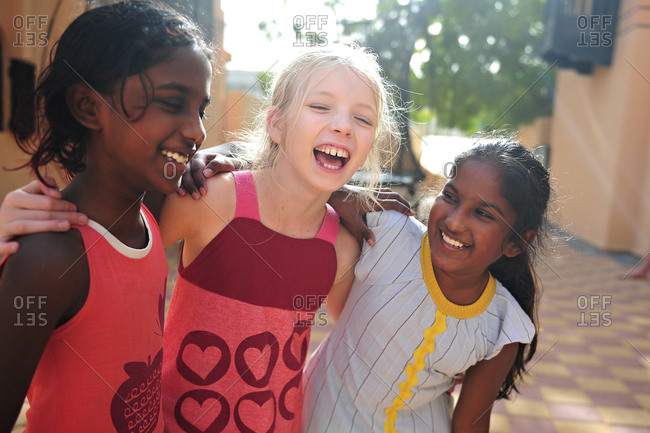 Three young girls of different ethnicities hugging each other and laughing