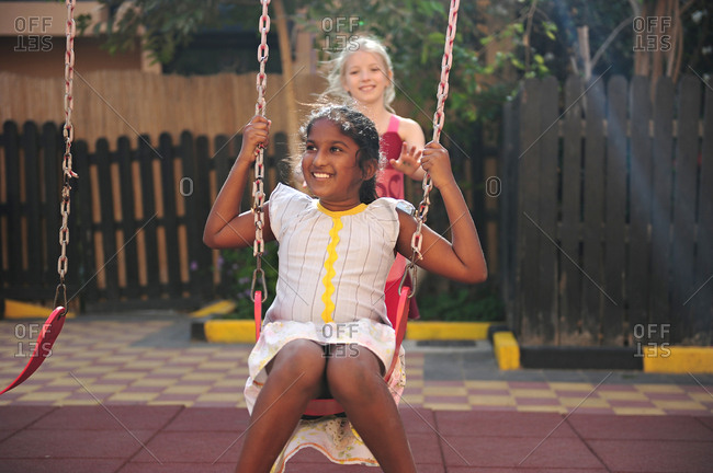 Young south Asian girl being pushed on swing by friend in playground