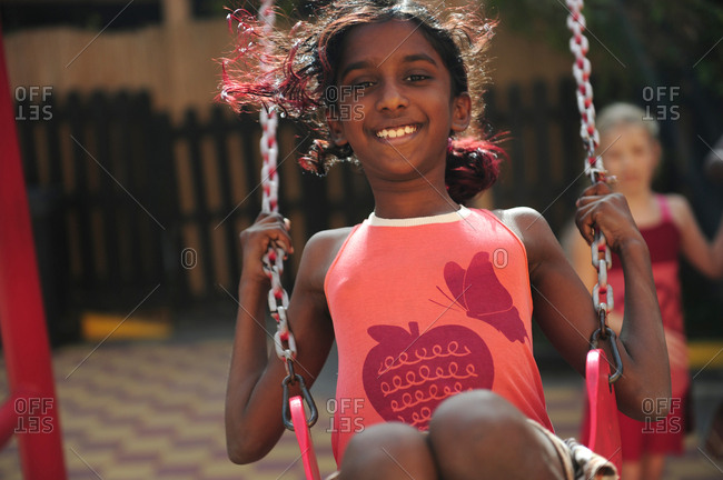 Close up of young Indian girl on swing in playground with friend in background