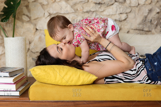 Mother lying on couch holding and kissing her baby
