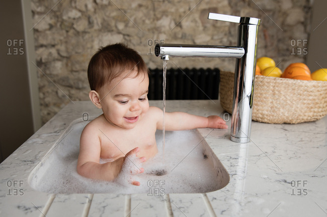 Baby Having A Bubble Bath In The Kitchen Sink Stock Photo