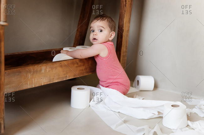 Baby making a mess while playing with toilet paper rolls