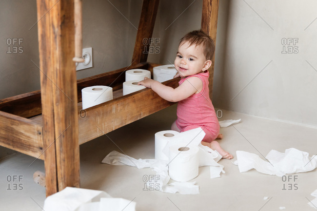 Baby playing with rolls of toilet paper