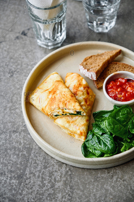 High angle view of omelet roll with ham and cheese with fresh spinach, tomato chutney slices of whole meal bread