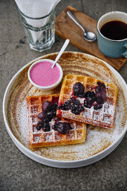 High angle view of waffles and blackberries sprinkled with confectioners sugar with a cup of black coffee