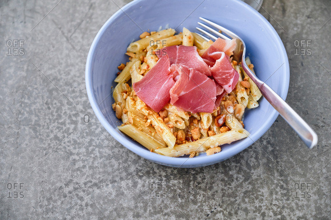 High angle view of humble bowl of penne pasta with prosciutto and peanuts