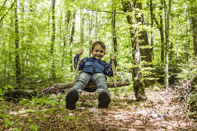 Happy kid on a swing amid a mountain trail