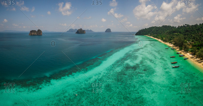 Panoramic aerial view of traditional long-tail boats moored in the bay of Chao Mai National Park in Thailand.
