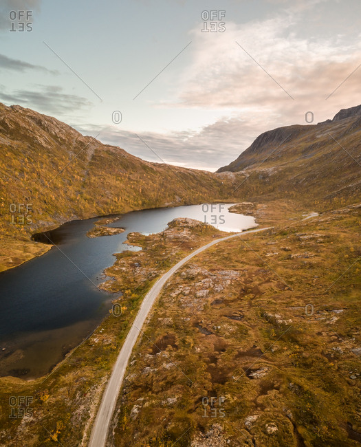 Aerial view of beautiful lake next to curvy mountain road in Norway
