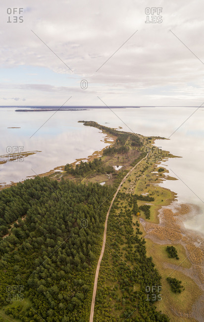 Aerial view of green coastline of Vormsi during cloudy weather in Estonia