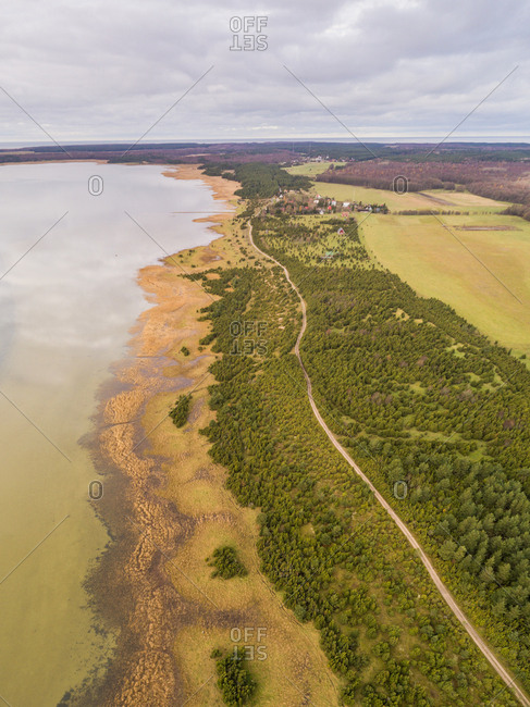 Aerial view of green coastline of Vormsi island during cloudy weather in Estonia