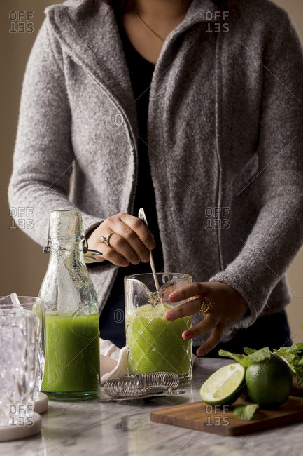 Woman making a Cucumber Lime Cocktail