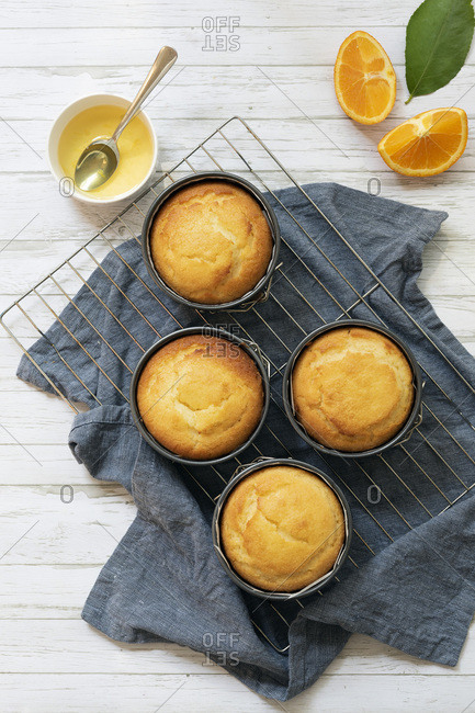 Four small round individual orange cakes in their tins cooling on a wire rack with a bowl of orange syrup.
