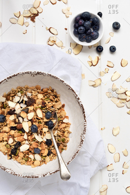 A bowl of wholegrain breakfast cereal with blueberries and almonds.