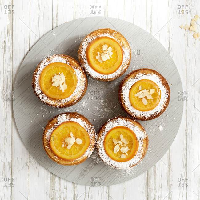 Individual round orange cakes topped with a slice of glazed orange, flaked almonds and powdered sugar served on a blue wooden board.