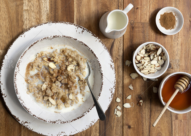 Traditional oatmeal porridge in a bowl with sliced almonds, cinnamon, honey and a jug of milk.