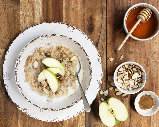 A bowl of organic oatmeal porridge with sliced apple on top and bowls of flaked almonds and cinnamon.