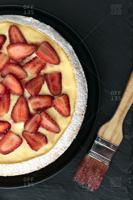 Strawberry custard dessert cake with a pastry brush.