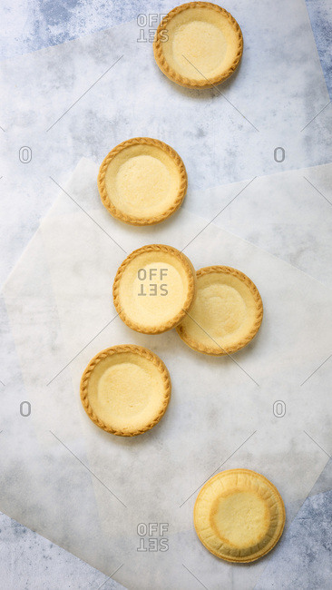 Small round cooked pastry cases on baking paper.